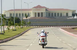 A police motorcycle approaches the President's Office in Naypyidaw, Myanmar, Dec. 1, 2011.