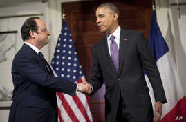 President Barack Obama, right, and French President Francois Hollande, left, shake hands after talking with the media following their tour of Monticello, President Thomas Jefferson's estate, Feb. 10, 2014, in Charlottesville, Virginia.