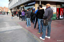 People queue outside a government-run job centre in Madrid, Spain, April 27, 2016.