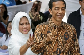 """Indonesian presidential candidate Joko Widodo, popularly known as """"Jokowi"""", left, and his wife Iriana, show their inked fingers after casting their ballots during the presidential election in Jakarta, Indonesia, July 9, 2014."""