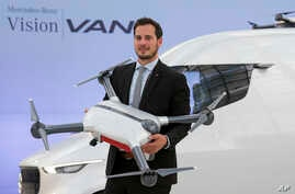 FILE - Frieder Soenning, employee of the Daimler AG, presents the Matternet Drone-equipped delivery van Mercedes Vision Van at the International Transport Forum 2017 in Leipzig, Germany, May 31, 2017.