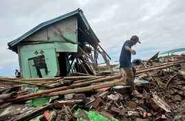 A man makes his way past a house badly damaged by a tsunami in Sumur, Indonesia, Dec. 24, 2018.