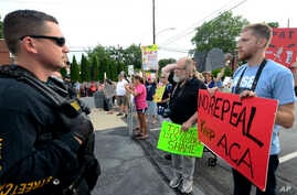 Watched by police, demonstrators against the Senate Republican health care bill await the arrival of Pennsylvania's U.S. Sen. Pat Toomey outside the studios of WHTM-TV, July 5, 2017 in Harrisburg, Pa.