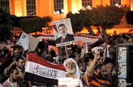 Egyptian supporters of the deposed president Mohamed Morsi hold his portrait and wave the national flags during a demonstration against the government in Cairo, July 31, 2013.