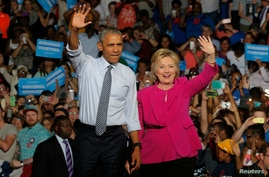 FILE - U.S. President Barack Obama stands with Democratic U.S. presidential candidate Hillary Clinton during a Clinton campaign event in Charlotte, North Carolina.