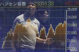 FILE - Passersby are reflected on in electronic graph showing recent movements of the Hang Seng Index outside a brokerage in Tokyo.