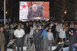 People congregate around a large TV screen  showing Algeria's President Abdelaziz Bouteflika in Algiers, April 15, 2011