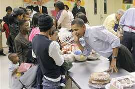 President Barack Obama leans over to listens to hear a child speak as he helps pack food for Thanksgiving at Martha's Table, a local food pantry in Washington, 24 Nov., 2010