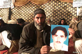 "FILE - Mohammad Bilal holds a picture of his son Hazratullah as he takes part in a protest with members of the Pashtun community against what they say are enforced ""disappearances"" and routine oppression, in Islamabad, Feb. 8, 2018."