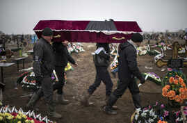 Ukrainian municipal workers carry a coffin bearing the body of Vitaliy Sirotenko, who was killed Saturday during an attack in Mariupol, Ukraine, on  Jan. 27, 2015.