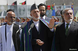 Afghan President Hamid Karzai (C) speaks during celebrations to commemorate Afghanistan's 95th anniversary of independence as he is flanked by presidential candidates Abdullah Abdullah (R) and Ashraf Ghani in Kabul, Afghanistan, Aug. 19, 2014.