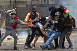 Demonstrators help a journalist who was injured in a leg while covering clashes between demonstrators and the  Bolivarian National Guard during a protest in Caracas, Venezuela, April 10, 2017.