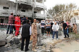 Libyan security forces gather outside the French embassy building in Tripoli following a car bomb attack, April 23, 2013.