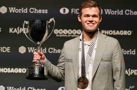 Reigning chess world champion, Norway's Magnus Carlsen celebrates with the trophy after retaining the World chess Championship in London, Nov. 28, 2018. Carlsen defeated American challenger Fabiano Caruana 3-0 in rapid tiebreaker games.