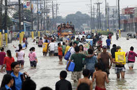 Residents wade through floodwaters on a street in Bacoor, Cavite near Manila, August 20, 2013.