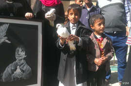 A blind child carries a dove at a protest against the attack on the al-Nour Center for the Blind on Jan. 10, 2016, in Sana'a, Yemen. Students say neither the school, nor themselves, have taken any side in the war. (A. Mojalli/VOA)