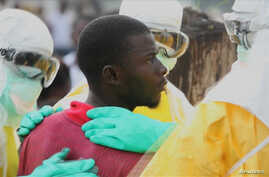 Health workers surround an Ebola patient who escaped from quarantine from Monrovia's Elwa hospital, in the center of Paynesville, September 1, 2014.