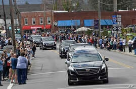 People line the street to pay respects as the hearse carrying the body of Rev. Billy Graham travels through Black Mountain, N.C., Feb. 24, 2018. The procession is part of more than a week of mourning that culminates with his burial next week at his l