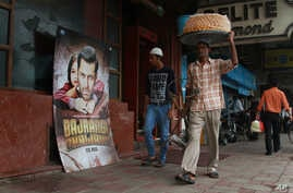 "An Indian vendor walks past a poster of Bollywood actor Salman Khan's latest movie ""Bajrangi Bhaijaan"" outside a theater in New Delhi, India, Aug. 11, 2015."