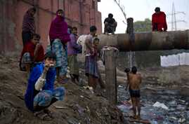FILE - Indian men attend to their morning chores next to a sewage canal before they leave for work early morning in New Delhi, India, Dec. 12, 2014.
