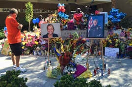 """A visitor pays his respect at a memorial for Palm Springs Police Officers Lesley Zerebny, and Jose """"Gil"""" Gilbert Vega."""