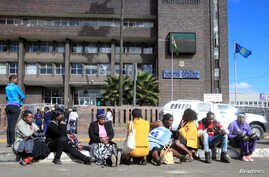 Zimbabweans wait outside the Harare Central Police station, in Zimbabwe, July 12, 2016, where Pastor Evan Mawarire (not in the picture), who organized a 'stay at home' anti-government protest last week appeared.