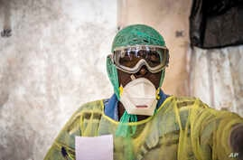 FILE - A health worker examines patients for Ebola inside a screening tent, at the Kenema Government Hospital in Sierra Leone.