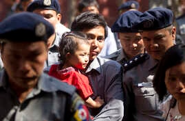 Reuters journalist Kyaw Soe Oo carries his daughter as he is escorted by Myanmar police to trial after a break, Feb. 1, 2018, outside of Yangon, Myanmar. A lawyer for the two Reuters journalists Wa Lone and Kyaw Soe Oo, charged with illegally handlin...