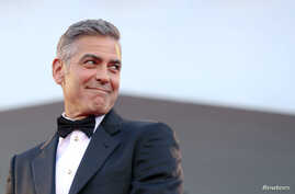 """U.S. actor George Clooney smiles as he arrives on the red carpet for the premiere of """"Gravity"""" at the 70th Venice Film Festival in Venice, August 28, 2013."""
