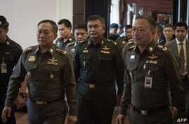 Thai Army Lieutenant General Manas Kongpan, center, is surrounded by police officers as he turns himself in at the police headquarters in Bangkok, June 3, 2015.