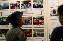 A Myanmar police officer looks at photos displayed during a press conference of Maungdaw Investigation Commission at a government guest house Sunday, Aug.6, 2017, in Yangon, Myanmar. The Myanmar government's inquiry into violence in northern Rakhine