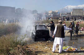 Pakistani firefighters extinguish a fire in a vechile at the site of a bomb explosion at a market in Parachinar, the capital of Kurram tribal district, Dec. 13, 2015.