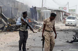Somali police walk around the scene of an explosion near the entrance of the airport in Mogadishu, Feb. 13, 2014.