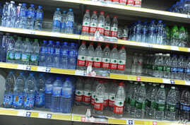 FILE - A picture shows a shelf full of various Chinese bottled water at a supermarket in Beijing. Random market inspections found bacteria colonies in the water, some containing bacteria levels 9,000 times above safety standards.