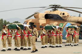 Pakistani army soldiers carry coffins, wrapped in national flags and carrying bodies of helicopter crash victims, at the Nur Khan air base in Islamabad, May 9, 2015.