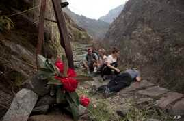 FILE - In this March 27, 2017 photo, Elizabeth Brenner, third right, and her family sit at the spot on the Milam Glacier Trail where Brenner's son, Thomas Plotkin, slipped and fell more than 300 feet down a steep gorge and into the raging Goriganga r