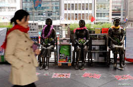 """Statues of """"comfort women"""" are placed outside Japan's consulate to commemorate the 80th anniversary of the Nanjing Massacre, in Hong Kong, China, Dec. 13, 2017."""