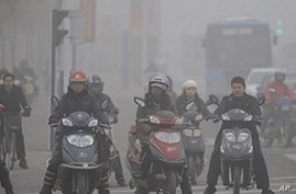 Chinese motorists ride their electric bikes in heavy fog down a street in Hefei, east China's Anhui province, 25 Nov 2009