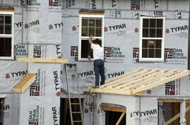 Workers continue construction on a housing complex in Zelienople, Pennsylvania, March 28, 2014.