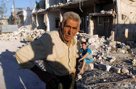 A man near his destroyed house after a recent Syrian Air Force air strike in Azaz, Syria, August 20, 2012.