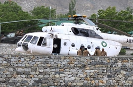 Pakistani soldiers gather beside an army helicopter at a military hospital where victims of a helicopter crash were brought for treatment in Gilgit, on May 8, 2015.