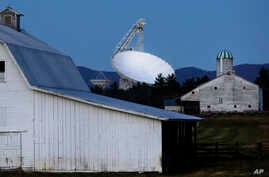 FILE - The Robert C. Byrd Green Bank Telescope towers over farmland as dusk falls in Green Bank, W.Va., Nov. 14, 2013.