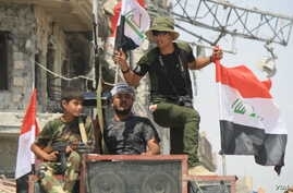Iraqi soldiers celebrate their victory over IS militants in Mosul as battles continue in the Old City, July 12, 2017.