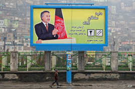 An Afghan boy walks past an election poster of a presidential candidate, Mohammad Daoud Sultanzai, in Kabul, Afghanistan, March 15, 2014.