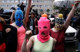 Russian punk group Pussy Riot members Nadezhda Tolokonnikova, in the blue balaclava, and Maria Alekhina, in the pink balaclava, make their way through a crowd after they were released from a police station, Feb. 18, 2014, in Adler, Russia.