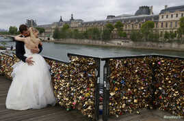 """A recently-married couple from Poland, Dominika and Bartek Mieczkowski, embrace near grills covered with """"love locks"""" on a walkway which leads to the Pont de Arts over the River Seine in Paris, France, May 31, 2015. On June 1, the bridge will be clos"""