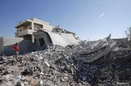 Civilians stand near a destroyed house in wake of early morning Syrian Air Force strikes, Aziz, Sept. 3, 2012.