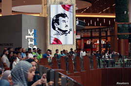 A painting depicting Qatar's Sheikh Tamim bin Hamad Al Thani is seen as people gather to watch players from Spain's national team in Mall of Qatar in Doha, July 5, 2017.