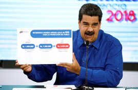 Venezuela's President Nicolas Maduro holds a banner explaining the new minimum wage as he speaks during a news conference in Caracas, Venezuela April 30, 2018.