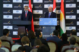 Turkish Energy Minister Taner Yildiz (L) and his Iraqi Kurdish counterpart Ashti Hawrami hold a press conference in Arbil, the capital of the autonomous Kurdish region in northern Iraq, Dec. 2, 2013.